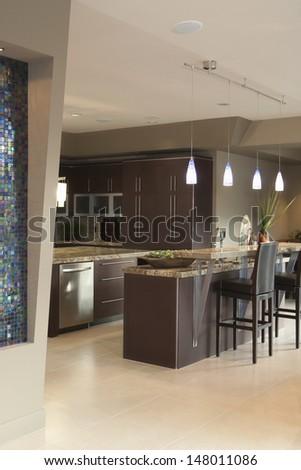 Dark brown kitchen with bar stools - stock photo