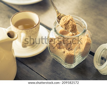 Dark brown sugar with cup of tea on wood table, retro color style - stock photo