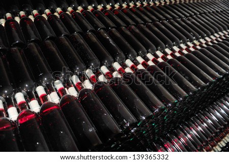 Dark cellar with old bottles of red wine - stock photo
