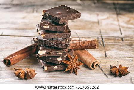 dark chocolate and cinnamon stick on wooden background