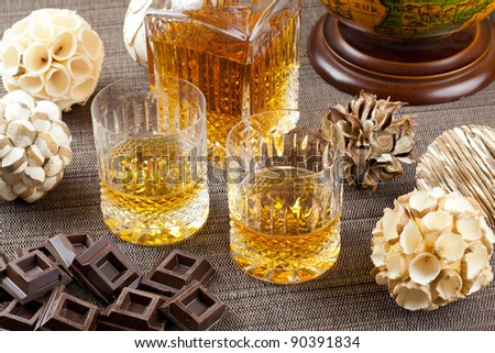Dark chocolate and fine scotch whisky in crystal bottle and tumbler glasses with stylish spheres and antique globe in background - stock photo