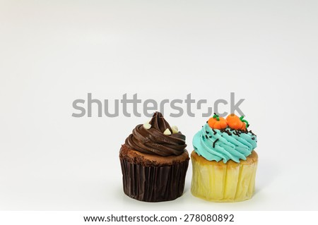 Dark chocolate and pumpkin face cupcakes on white background