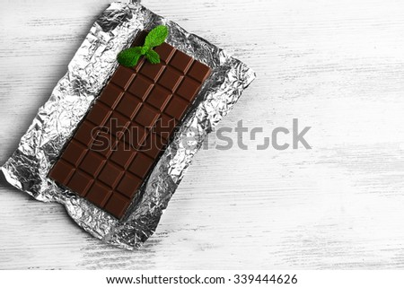 Dark Chocolate bar in foil  on gray background - stock photo