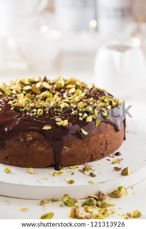 Dark chocolate cake with cardamom and covered with pistache and chocolate ganache
