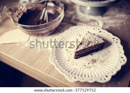 Dark chocolate cake with icing powdered sugar on top served on a cute little vintage ceramic plate.Homemade chocolate cake served with mess in the background of making the cake.Calories and sugars - stock photo