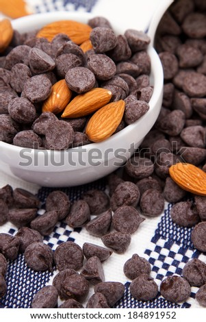 Dark chocolate chips and almonds on checkered tablecloth - stock photo