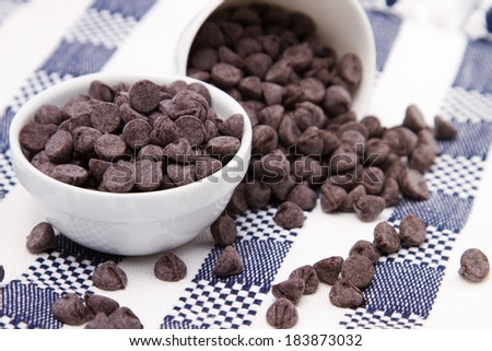 Dark chocolate chips in white bowls on checkered tablecloth - stock photo