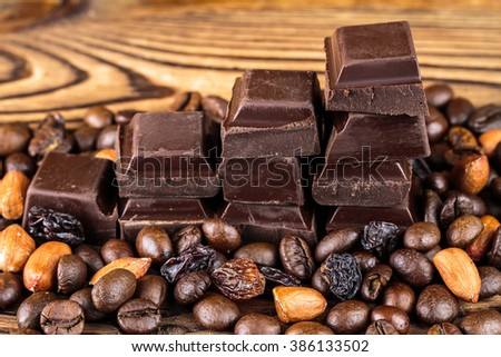 Dark chocolate cubes, coffee beans, peanuts and raisins on wooden table, close-up, selective focus