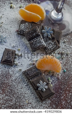 Dark chocolate tablets with fresh mandarin slices with sugar powder and silver snowflakes