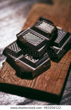 dark chocolate tabs on a small chopping board on a wooden table
