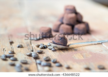 Dark chocolate truffles with cocoa powder, coconut and chopped hazelnuts on a wooden table. - stock photo
