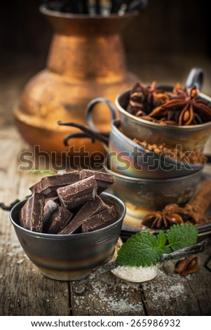 Dark chocolate, vanilla, vanilla sugar, cocoa powder, aniseed wearing vintage silver cups on a wooden natural background with a coffee pot in the background. selective Focus - stock photo