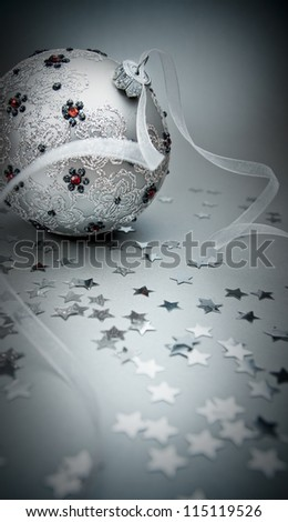 dark christmas decoration with christmas bauble, ribbon and stars - stock photo