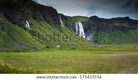 Dark cliff with waterfalls in Iceland and grass