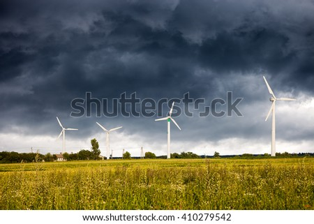 Dark clouds above a Wind Turbines. - stock photo