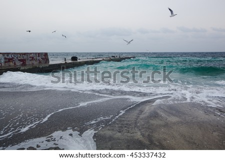 Dark clouds and crashing ocean waves during storm - stock photo
