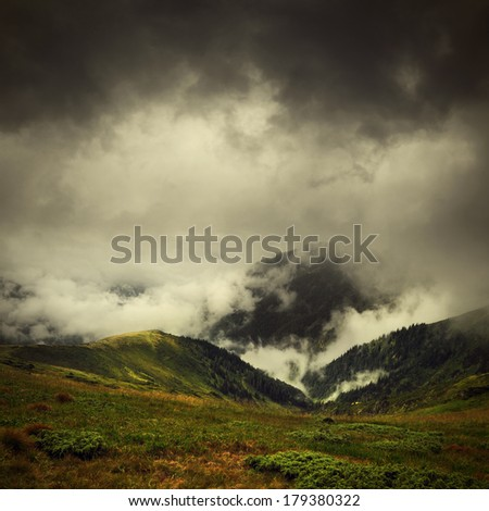 dark clouds and fog over mountain valley, summer Carpathians landscape  - stock photo