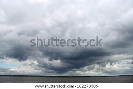 Dark clouds over the river - stock photo