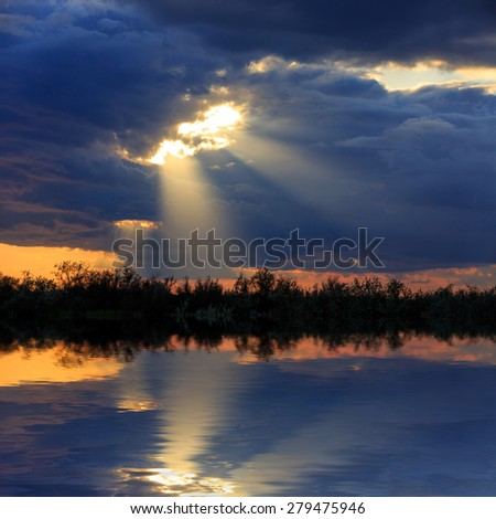 Dark clouds with sun rays over lake water - stock photo