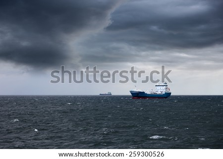 Dark cloudy stormy sky with ship and waves in the sea. - stock photo