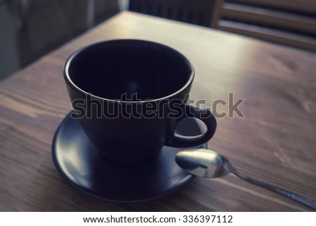Dark colored cup of coffee in a brown cup on wooden background. Cup of coffee on wooden table. Photo in old color image style instagram filter - stock photo