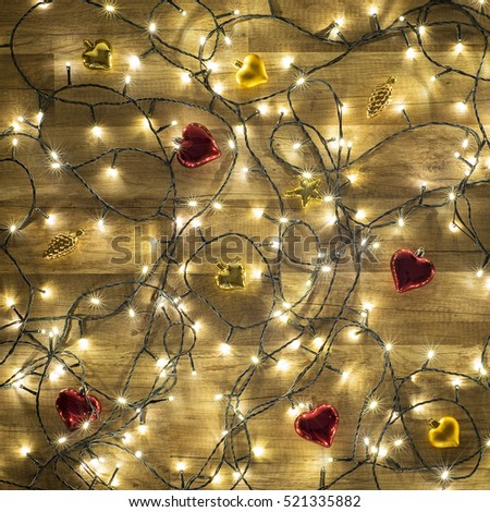 Dark Colorful Christmas background, garland lights on wooden floor with glitter baubles and tinsel