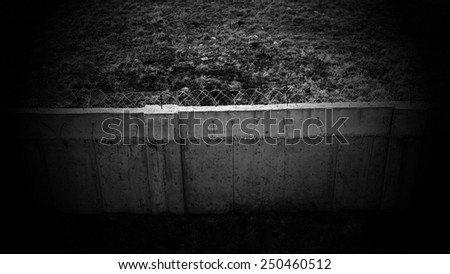dark concrete wall with barbed wire - stock photo