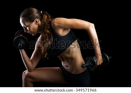 Dark contrast shot of young beautiful fitness woman with beads of sweat which training in gym. Working out with dumbbells on black background - stock photo