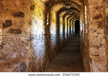 Dark corridor in dungeon with light in the end - stock photo