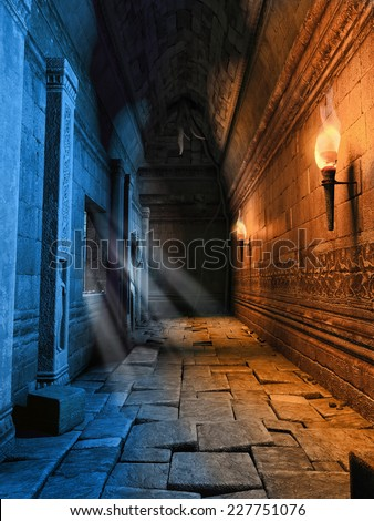 Dark corridor with burning torches in a ruined building - stock photo