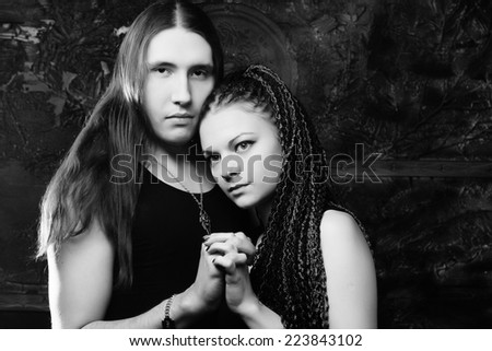 Dark couple - young woman and young man - stock photo