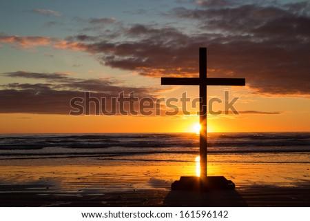 Dark cross at beach as the sun sets over the sea. - stock photo