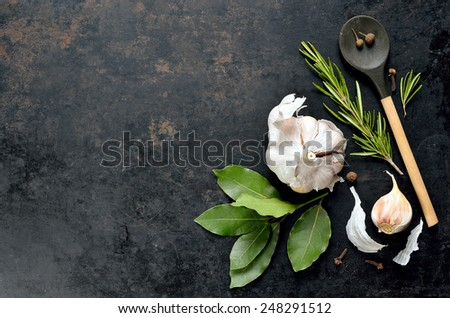 Dark culinary background with a wooden spoon along with garlic, rosemary, bay leaves,  pepper and some cloves pictured on it - stock photo