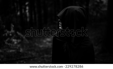 Dark demon in dark forest. Grim reaper in search of his victim. Death coming for his soul. Woman devil in black cape and hood - stock photo