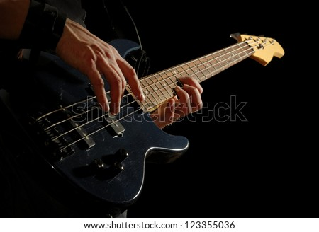 dark electrical bass guitar in male hands, on black background - stock photo