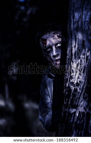 Dark evil portrait of a creepy zombie man peering from behind trees in a night forest. The watcher - stock photo