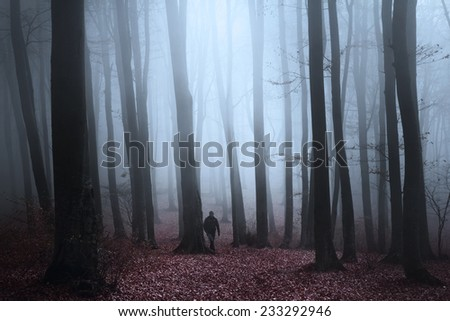 Dark foggy forest with black silhouette of a man - stock photo