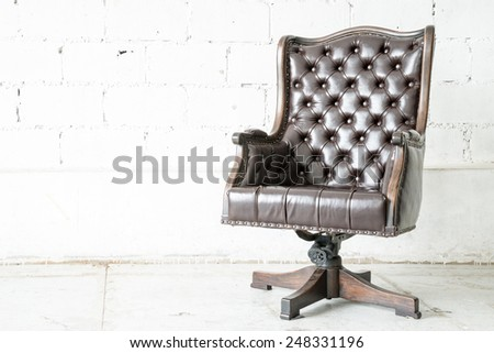 Dark genuine leather classical style sofa in vintage room - stock photo