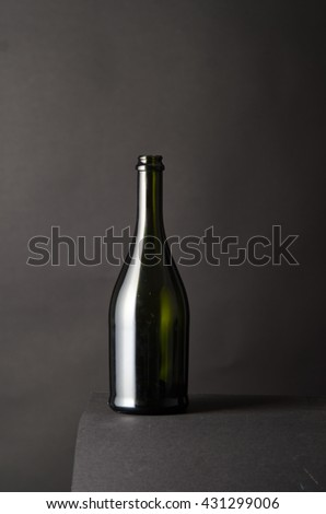 dark glass wine bottle on a gray background, vertical frame, studio shot, empty space for placing text, to winemakers