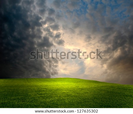 Dark gloomy evening with a bright lush meadow - stock photo