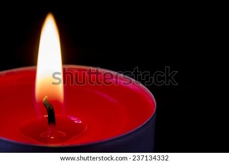 Dark glowing red tea light - stock photo
