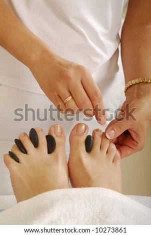 Dark gray stones in the woman foot - stock photo