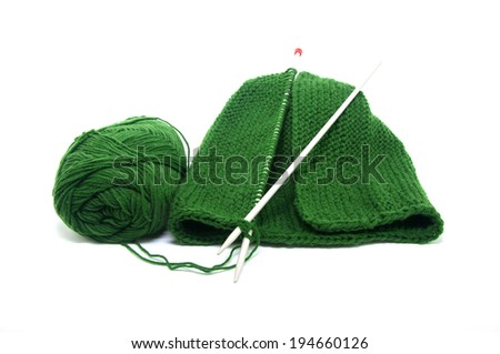 Dark green knit hat unfinished on white background.