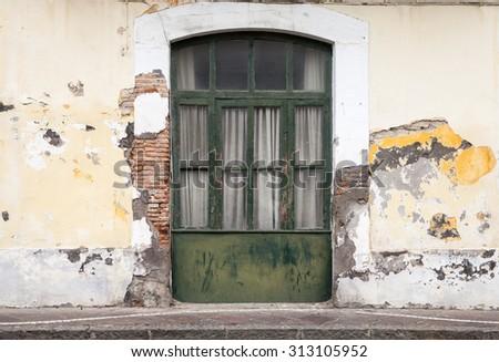 Dark green wooden door in old building facade. Ischia, Italy - stock photo