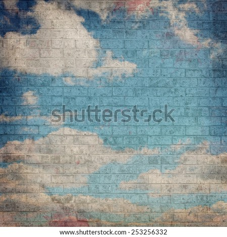 Dark Grunge image of a Blue Sky with Clouds painted on a Brick wall - stock photo