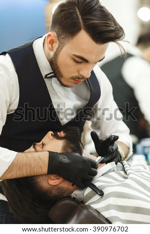 Dark haired barber wearing black gloves making a beard form with razor for man with dark hair and beard at barber shop, portrait, close up.