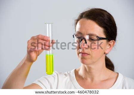 dark haired female lab assistant with test tube