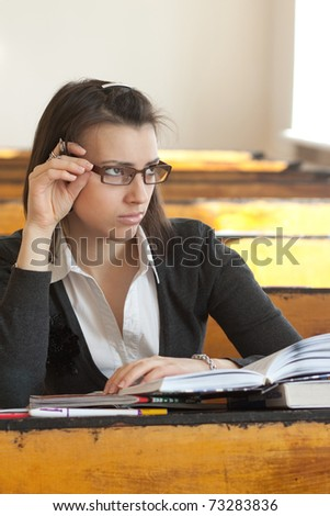 Dark-haired female student with glasses sitting at a desk - stock photo