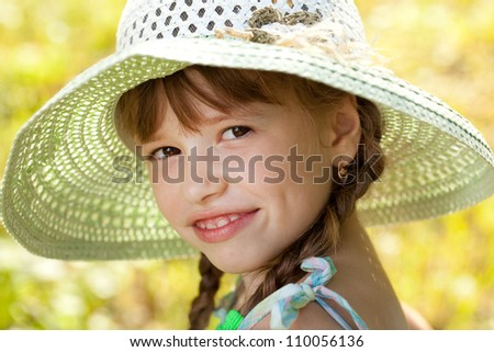 Dark-haired girl in a hat and dress smiling