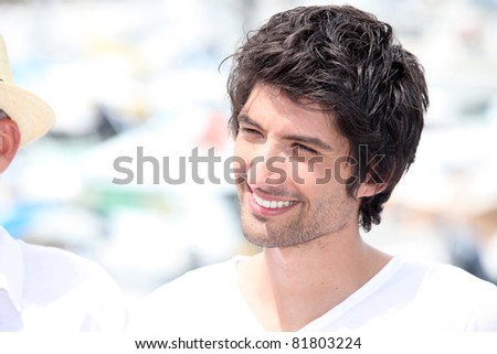 Dark haired man in white t-shirt stood outdoors